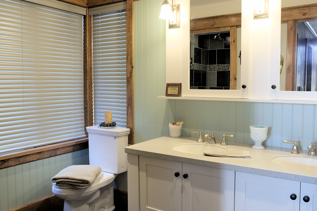 Casual bathroom featuring a double sink white vanity/mirror combination with contrasting dark knobs.