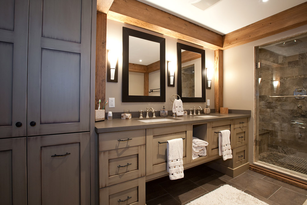 This rustic bathroom vanity features ample storage and is highlighted by the wood beams and contrasting dark mirrors.