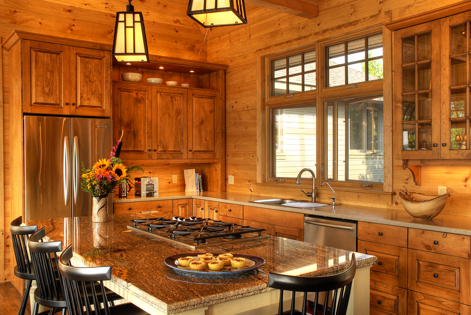 A warm, cozy cottage kitchen on Georgian Bay with medium tone pine cabinets and a contrasting beige island.
