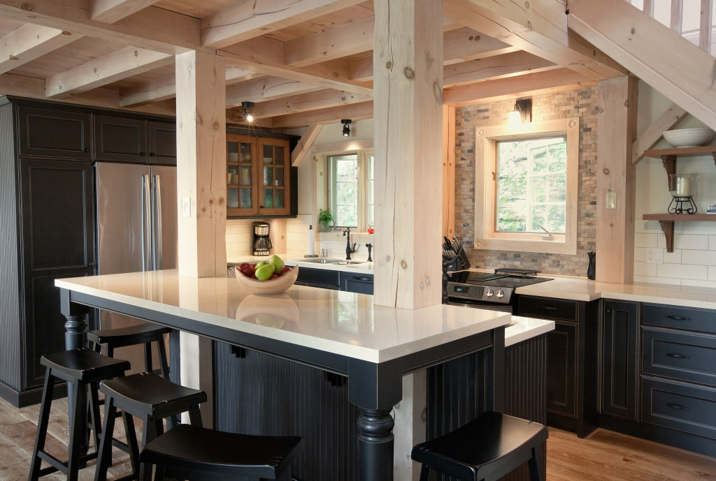 A rustic black cottage kitchen with contrasting off white countertops and touches of medium wood accents.