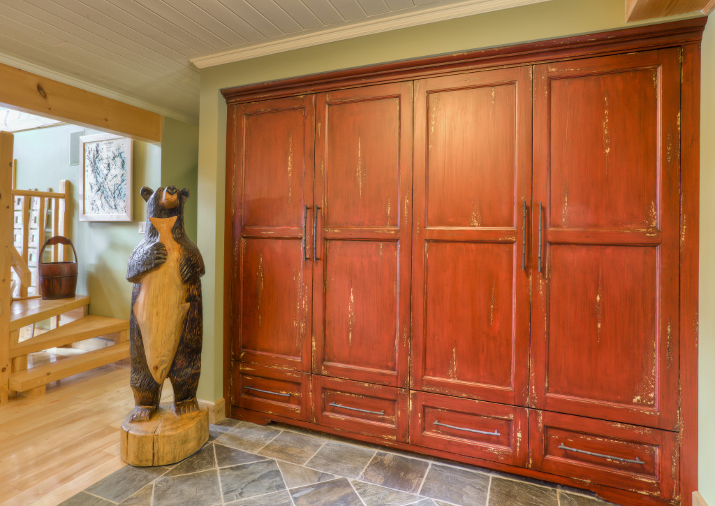 Rustic painted entry cabinets in this cottage in Muskoka accommodate all your storage needs.