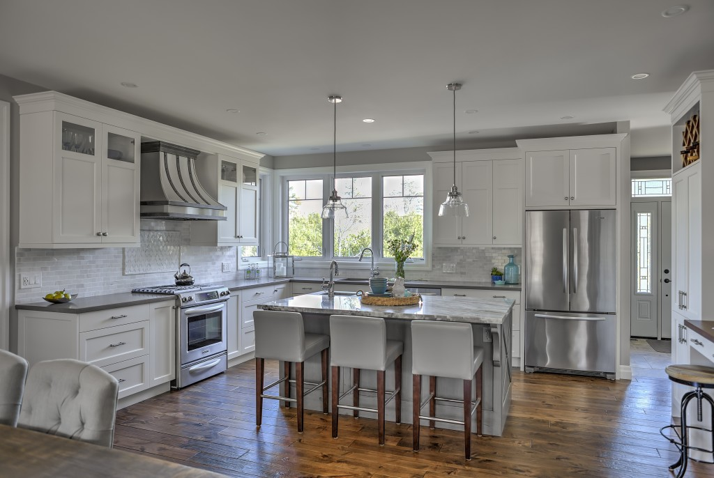 A fresh kitchen with a mix of cool grey countertops, white cabinets and rich brown natural wood floors.