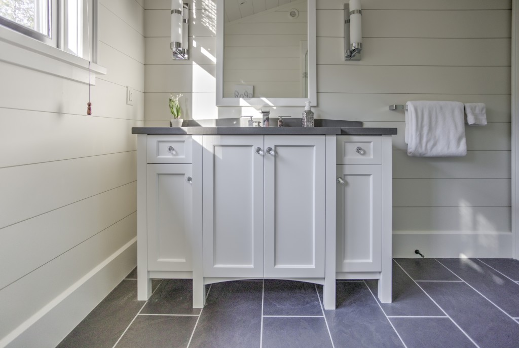 Custom bathroom vanity with soft white cabinets and contrasting grey countertops.