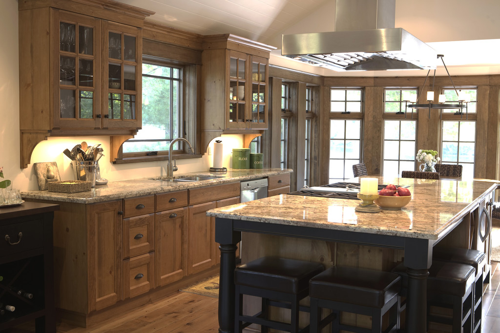 A warm, medium wood tone kitchen with beige countertops and dark wood accents that frame the island base.